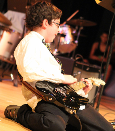 Boy Playing Gutiar On Stage On His Knees