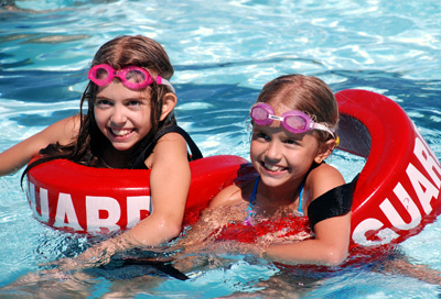 Free Swim Every Afternoon Shows Two Girls with life Guard Floats around them swimming.