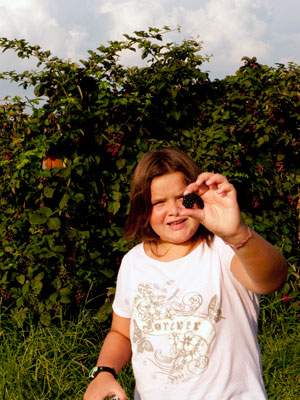 Organic gardening. Young Girl showing small organic insect from the ground
