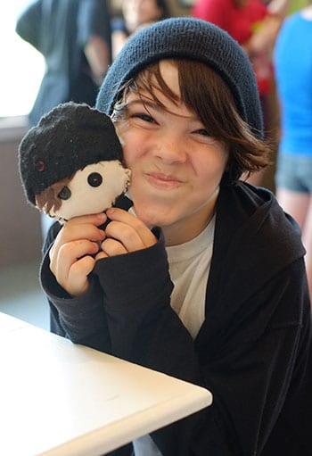 Shows A Young Child Holding a very cute stuffed doll that looks like a young boy.