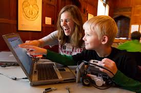 Adult Showing young Boy Computer while holding design lego