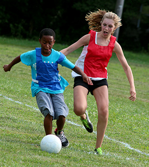 Boy and Girl Playing Soccer Ball. Girl about to kick ball from behind